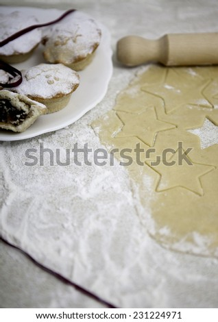Christmas mince pies with pastry on the floured surface  - stock photo
