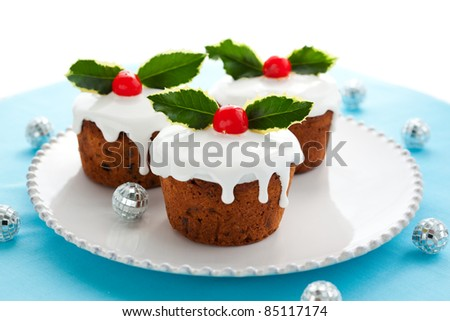 Christmas mini  cakes with holly leaves and berries - stock photo