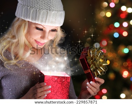 Christmas Miracle. Smiling Blonde Girl Opening Gift Box over lights of Christmas tree  - stock photo