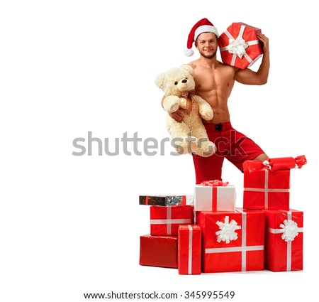 Christmas miracles. Handsome Santa Claus posing in a pile of presents with a teddy bear and a gift box copyspace on the side