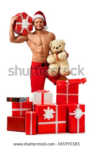 Christmas mood. Handsome Santa Claus smiling happily standing near present boxes holding plush teddy bear and a gift box