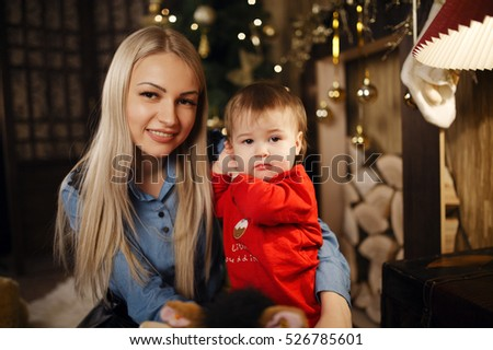 Christmas mood, the first new year baby, mother and daughter near a Christmas tree with gifts