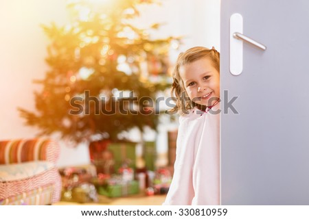 christmas morning, a lovely little girl opens a door, looking at the camera. in the background a Christmas tree decorated with gifts in his foot. The sun through the window gives a cozy atmosphere - stock photo