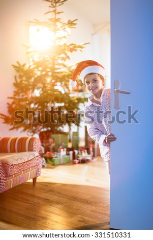 christmas morning,A lovely little girl with a Santa Claus hat opening a door,looking at the camera, behind her a Christmas tree decorated with a lot of gifts in his foot. The sun gives cozy atmosphere - stock photo