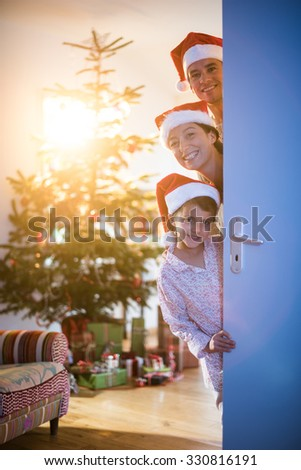 christmas morning, Dad Mom and daughter wearing a Santa Claus hat opening a door,looking at the camera, behind them a Christmas tree decorated, with gifts in his foot. The sun gives cozy atmosphere - stock photo