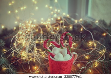 Christmas Mug filled with  hot cocoa drink decorated with candy cane and marshmallows,   on background with fir-tree. Toned image. - stock photo