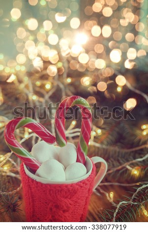 Christmas Mug filled with  hot cocoa drink decorated with candy cane and marshmallows,  on glitter  background with fir-tree. Toned image. - stock photo