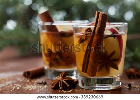 Christmas mulled apple cider with spices cinnamon, cloves, anise and honey on rustic table, traditional drink on winter holiday, magical evening light, selective focus - stock photo