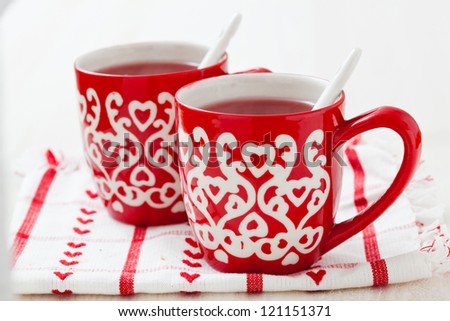 Christmas mulled wine in two small red cups resting on teatowel against white background - stock photo