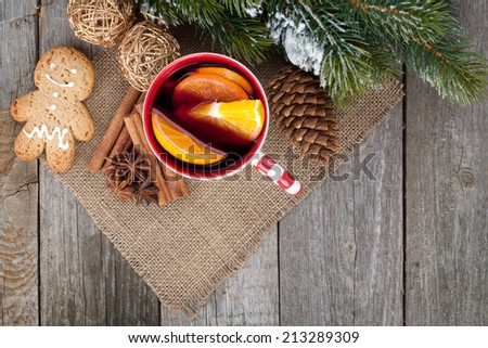 Christmas mulled wine with fir tree, gingerbread and spices on wooden table - stock photo