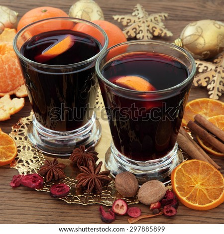 Christmas mulled wine with spices, fruit and gold baubles over oak background. - stock photo
