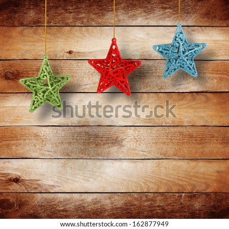 Christmas multicoloured stars on old wooden background