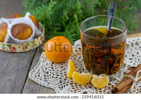 Christmas (New Year) composition. Glass cup of tea with mint, tangerine slices, cinnamon sticks, small cakes and thuja branches on wooden background - stock photo
