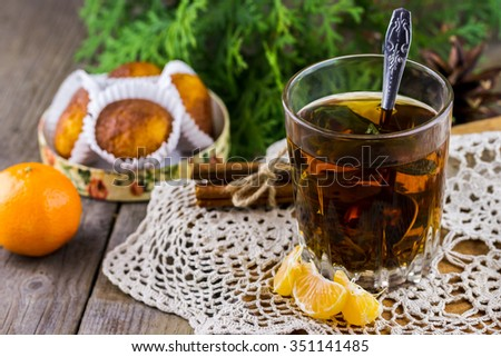 Christmas (New Year) composition. Glass cup of tea with mint, tangerine slices, cinnamon sticks, cupcakes and thuja branches on wooden background - stock photo