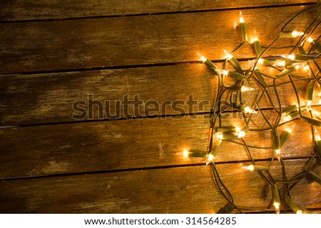 Christmas / New Year fairy lights on a wooden table to be used as background or texture. - stock photo