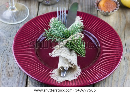 Christmas (New Year) table appointments. Fork and knife decorated thuja branches and twine bow on wooden background - stock photo