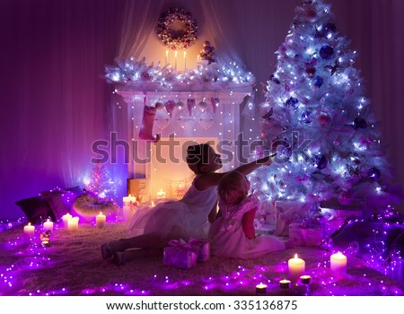 Christmas Night Room Kids under Lights Tree, Children Girls Looking Presents Gifts in Decorated Home - stock photo