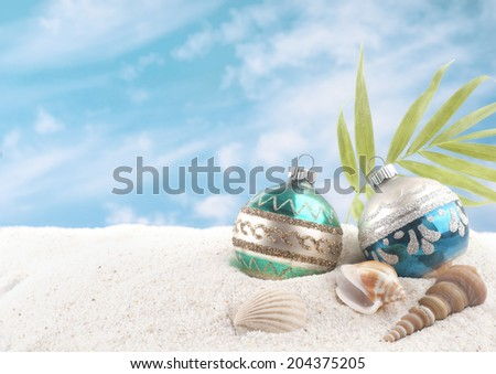Christmas on the Beach with Two Vintage Ornaments, Sea Shells and palm frond.  White sand and blue sky with clouds as background with room or space for copy, text, words.  Horizontal - stock photo