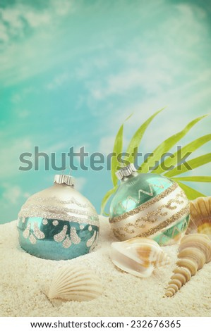 Christmas on the Beach with Two Vintage Ornaments, Sea Shells and palm frond. White sand and blue sky with clouds as background with room or space for copy, text, words. Vertical instagram warm tint  - stock photo