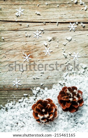 Christmas or Advent pine cone background with snow and failing snowflake decorations on a weathered rustic wood background with copyspace - stock photo