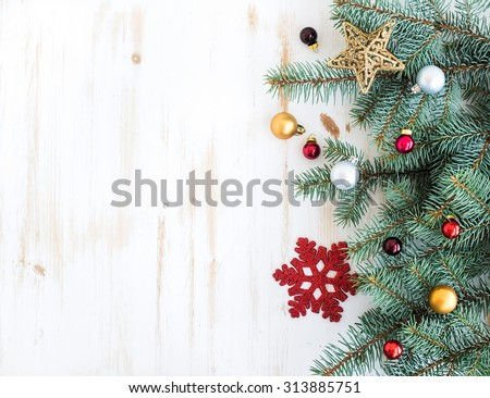 Christmas or New Year decoration background: fur-tree branches, colorful glass balls and glittering stars on white wooden background, top view, copy space - stock photo