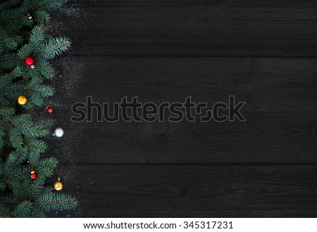 Christmas or New Year decoration background: fur-tree branches, colorful glass balls on black wood background with copy space - stock photo