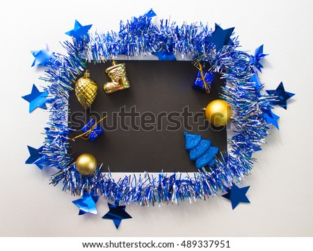 Christmas or New Year flat composition for writing or lettering. Blue sparkling ribbon wreath. Gold fir tree ornament and blue gift. Black paper with blank page. Season background for winter holidays