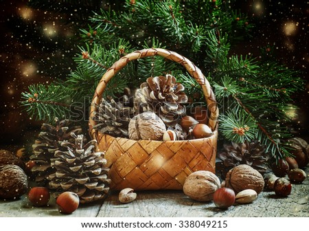 Christmas or New Year greeting card with a wicker basket with pine cones, fir branches, walnuts, hazelnuts and pistachios on the old wooden background, vintage style, selective focus - stock photo