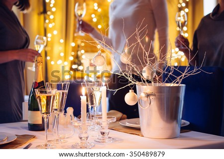 Christmas or New Year party table with champagne. Three persons stand behind - stock photo