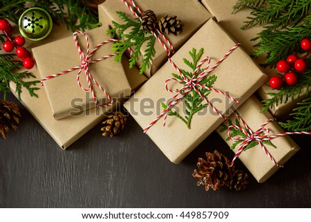 Christmas or New Year presents wrapped in natural colored paper and decorated with traditional Xmas twine and fir twigs on a dark background - stock photo