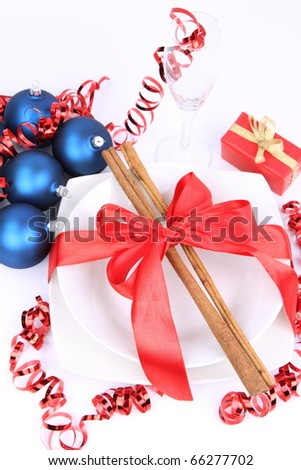 Christmas or New Year's setting - a plate decorated with cinnamon sticks and ribbon, a glass, christmas balls, candles, gift and cones