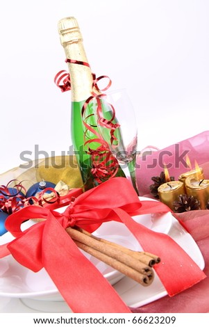 Christmas or New Year's setting - a plate decorated with ribbon and cinnamon sticks, a bottle of champagne, a glass, candles, christmas balls - stock photo