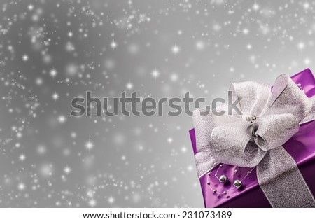 Christmas or Valentine's purple gift with silver ribbon abstract silver background - stock photo