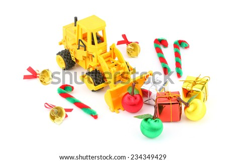Christmas ornament and decoration with old yellow toy tractor, canes, gift boxes and christmas balls on white background : Preparation for Chirstmas concept - stock photo