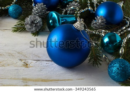 Christmas ornament blue balls, fir branches, silver fir cones, bells on a white wooden background, selective focus, close up, Christmas decoration, Merry Christmas - stock photo