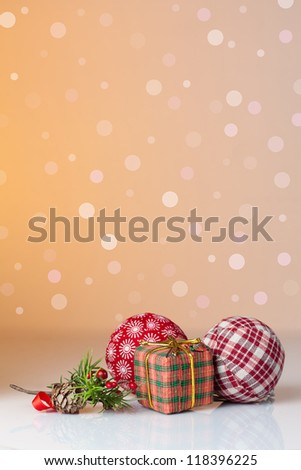 Christmas ornament: Christmas gifts in colorful wrapping with golden ribbons and christmas balls with a background of defocused lights - stock photo