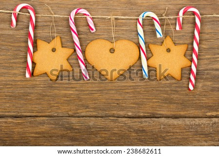 Christmas ornament - gingerbread, candy cane, rope with wood hooks on old wooden background - stock photo
