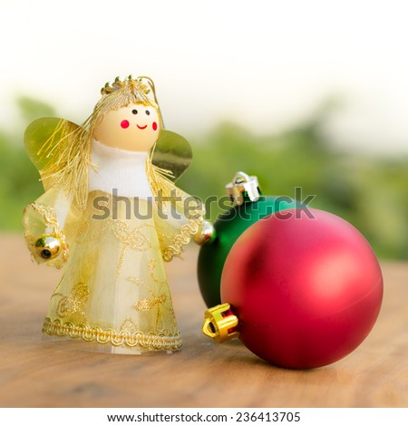Christmas ornament green and red balls with fairy in golden dress on soft background - stock photo