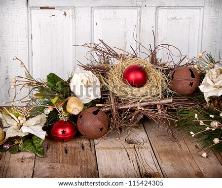Christmas ornament in a nest and pine branches on wooden background - stock photo