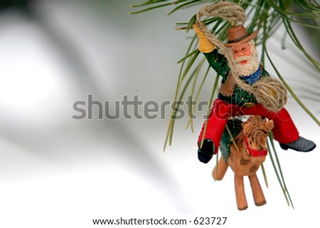 Christmas Ornament on pine tree in snow (Cowboy Santa) - stock photo