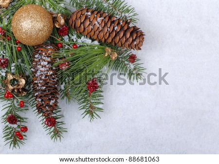 Christmas ornament with evergreen branches and pine cones on a white snowy background - stock photo