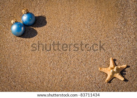 Christmas ornaments and yellow starfish on sand close up near the water