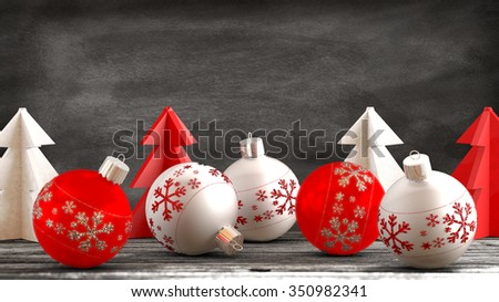 Christmas ornaments, balls, paper trees on a wooden table in front of a blackboard background. Copy space available. - stock photo