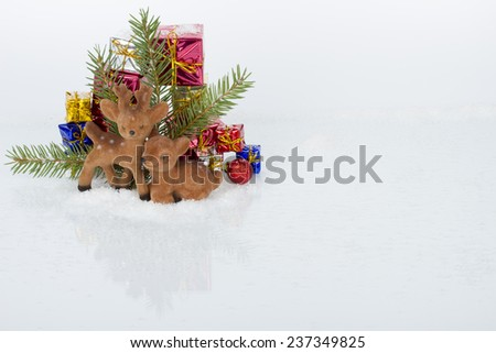 Christmas ornaments - deers on ice and snow with pine branches and gifts boxes on white background - stock photo