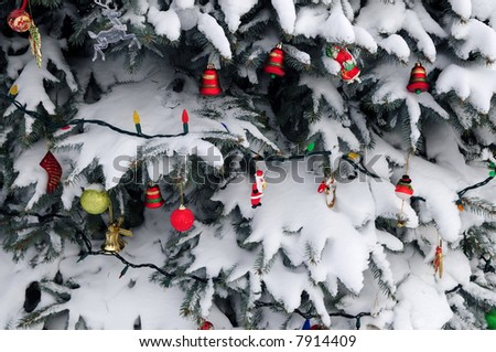 Christmas ornaments hanging on snow covered spruce tree outside - stock photo