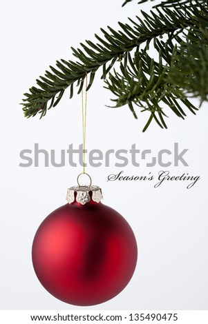 Christmas Ornaments hanging on tree with 'season's greeting' - stock photo