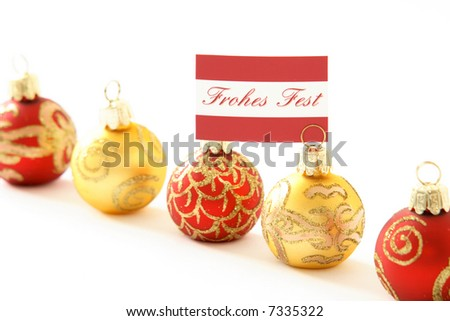 "Christmas ornaments, one with the German message ""Frohes Fest"" (Merry Christmas), with room for further text, shallow depth of field"
