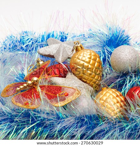 Christmas ornaments, silver stars, golden pine cones, balls and red lanterns, colored tinsel.