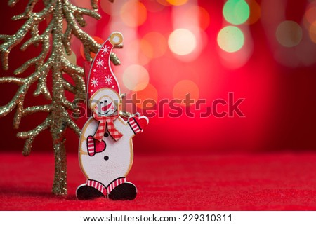 Christmas ornaments snow man and tree with blurry glitter shiny lights at background, copy space at side.  - stock photo