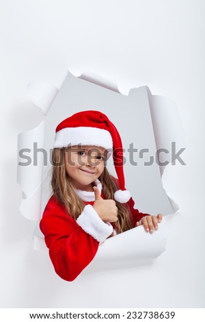 Christmas outfit girl giving thumbs up sign - leaning out of a jagged edge hole in paper layer - stock photo